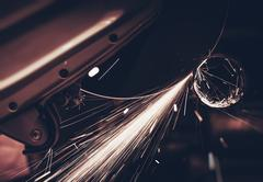 Metal Works Cutting Machine in Action. Metal Pipe Cutting with Sparks. - stock photo