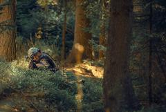 Military Operation in Forest. Soldier with Assault Rifle Laying Covered - stock photo