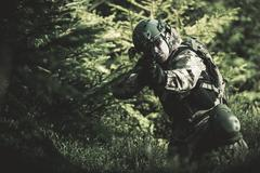 Special Forces Soldier. Camouflaged Marine Soldier Shooting Assault Rifle. Stock Photos