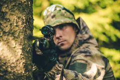Wildlife Hunter with Rifle Spotting Deer. Hunter Poacher Concept Photo. - stock photo