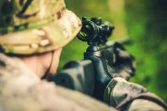 Wildlife Hunting. Camouflaged Hunter with Powerful Rifle with Scope Spotting - stock photo