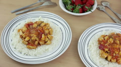 Panning shot of two steaming hot plates of sweet and sour chicken with rice Stock Footage