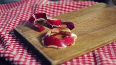 Apple peel falling down on wooden board. Peel of red apple - stock footage