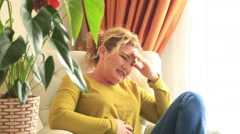 Woman having a painful stomach ache and sitting on couch with hands on abdomen - stock footage
