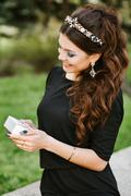 Stylish girl holding a gift. Wearing a black dress, expensive jewelry, ring - stock photo