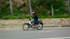 Motorcycle cruises around a curve on an otherwise empty highway in Nha Trang Stock Footage