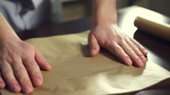 Preparing for baking cake. Cook putting baking paper on baking pan Stock Footage
