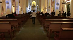 Visitors enter St. Anthony's Church and sit in the pews, in Macau, China. Stock Footage