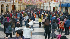 Large crowd of tourists strolling through a busy shopping area in Macau Stock Footage