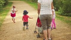 Little Children Take a Walk Through a Park Stock Footage