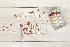 matchstick and matchbox on wooden background - stock photo
