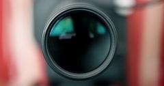 Defocussed Camera Lens Zooms into Focus - Photographer / Camera Operator Working Stock Footage