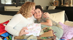Cute boy offering gift to her mother in the living room 4 - stock footage