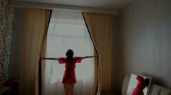 Young woman opening curtains in a bedroom Stock Footage