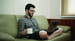 A guy using a laptop and drinking coffee Stock Footage
