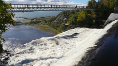Wide view reveals a long bridge above the Montmorency Falls in Quebec City Stock Footage