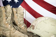 Old combat boots and helmet with American flag - stock photo