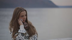The young beautiful woman is talking on the mobile phone concentrated on the Stock Footage