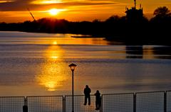 Observers on a fence watching the sunset on Ada lake in Belgrade - stock photo