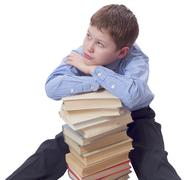 Young boy in classic  dress sitting with heap of books Stock Photos