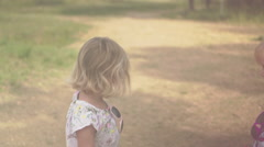Two Little Girls Take a Walk Through a Park Stock Footage