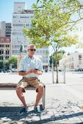 Mature male tourist resting on a city bench - stock photo