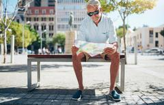 Senior tourist reading a city map - stock photo