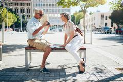 Senior tourist sitting on a bench looking pictures on camera - stock photo