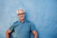 Mature man standing against a blue wall - stock photo