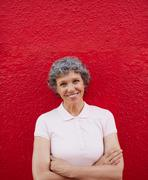 Happy senior woman standing against red background Stock Photos
