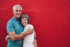 Affectionate mature couple together on red background - stock photo