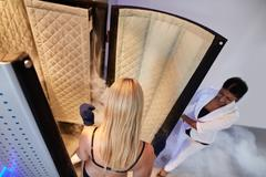 Woman entering Cryo sauna for whole body cryotherapy Stock Photos