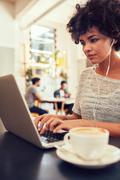 African woman at a coffee shop using laptop. - stock photo