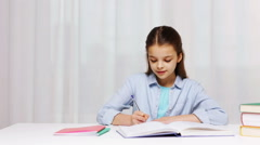 Happy school girl with books and notepad at home Stock Footage