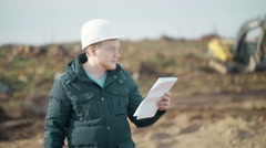 Engineer Talking Mobile Phone and Looking Documents on Background of Excavator Stock Footage