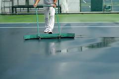 cleaning crew drying tennis court after rain - stock photo