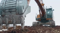 Excavator is digging the  frozen ground in winter day Stock Footage