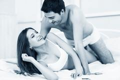 Young passionate couple in bed - stock photo