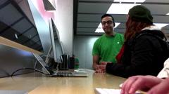 Woman sending message for her friend inside Apple store Stock Footage