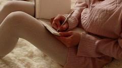 Beautiful woman writing in her diary Stock Footage