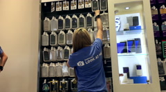Worker stocking cell phone cover for sale at samsung store - stock footage