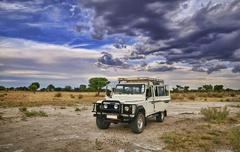 A 4 x 4 safari Vehicle in the Kalahari desert with beautiful cloudy sky. Stock Photos