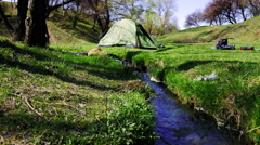 Stedycam shot of green tent near forest stream Stock Footage