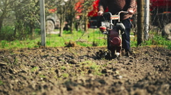 Old farmer working with cultivator tiller in garden - stock footage