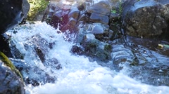Small rapids with fast moving water running beside rocks 2 Stock Footage