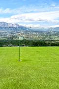 Small golf course amidst beautiful scenery with mountains Stock Photos