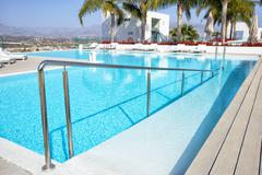 Swimming pool area with  white sun beds. Stock Photos
