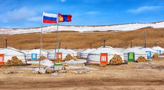 Russian and Mongolian flag next to gers (yurts) - stock photo