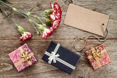 Three gift boxes,carnation and blank tag Stock Photos