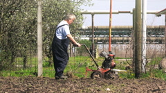 Old farmer working with cultivator tiller in garden Stock Footage
